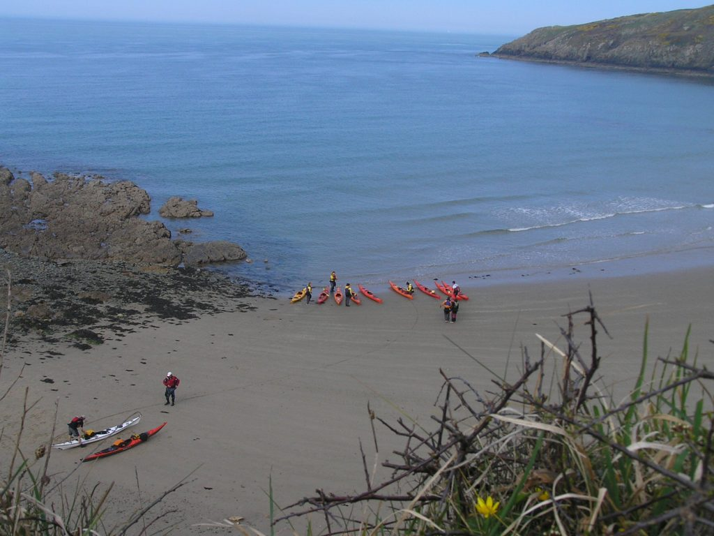 11 red kayaks on the beach at church bay