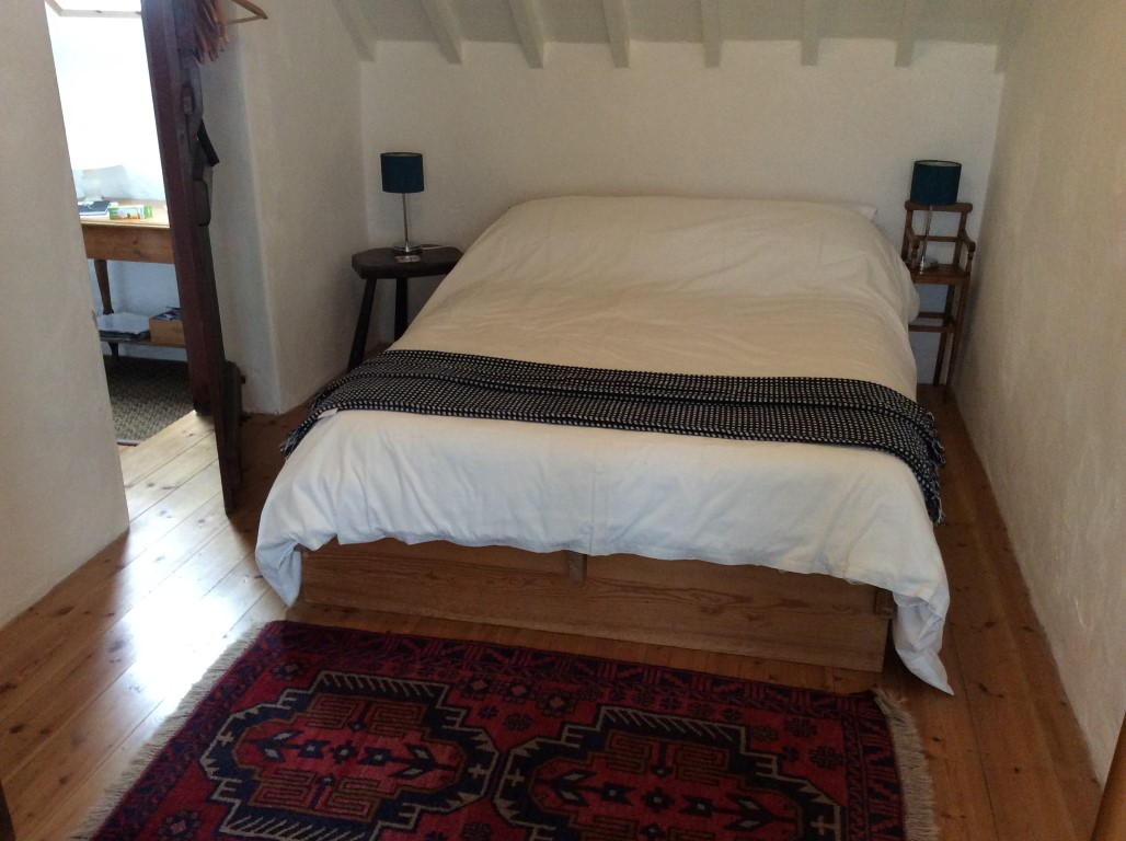 double bed with crisp white bed linen in barn apartment B&B Anglesey