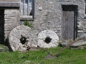 two mill stones and an old plough outside Llynnon water Mill