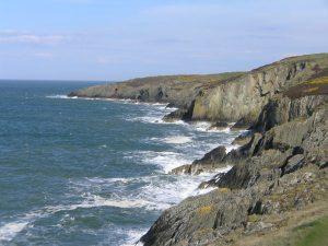 churning sea below jagged cliffs
