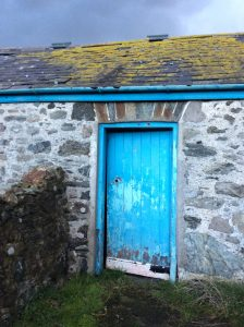 stone outbuilding with old blue barn door and lichen covered slate roof
